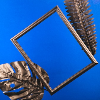 Black photo frame and leaves on a blue desktop.