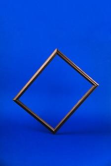 Black photo frame and leaves on blue desktop.