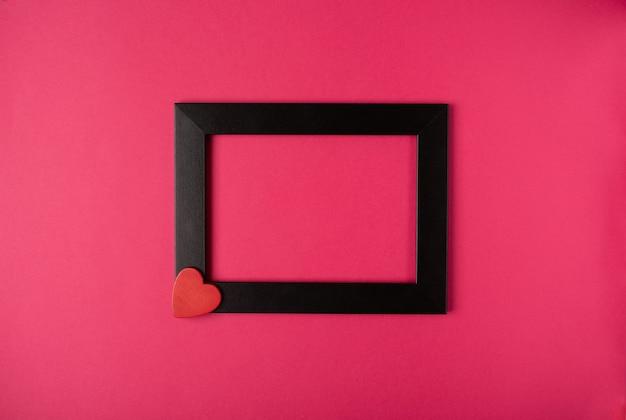 핫 핑크 바탕에 붉은 마음으로 검은 사진 프레임. 발렌타인 데이 개념. 평면 위치, 평면도, 텍스트를위한 공간.