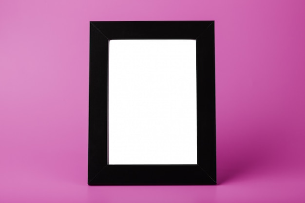 Black photo frame with an empty space on a pink background.