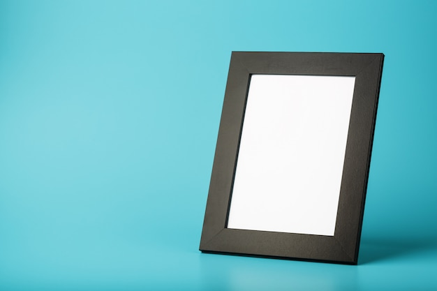Black photo frame with free space on a blue background.