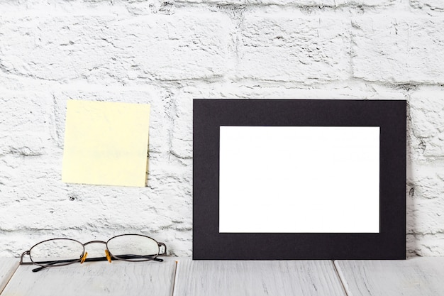 Black photo frame on wooden shelf or table. mockup with copy space