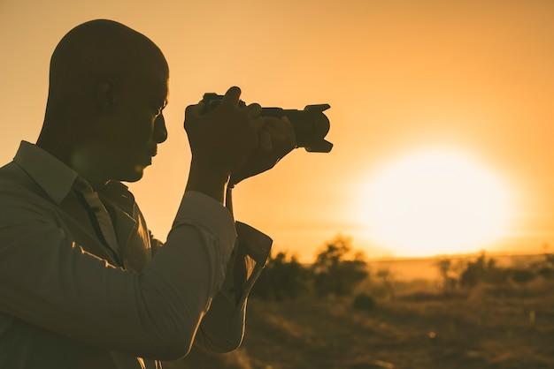 Черный фотограф фотографировать на закате с копией пространства.