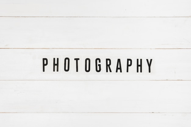 Black photography text on white wooden table