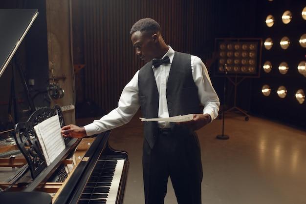 スポット ライトのあるステージで、音楽ノートを手にした黒人ピアニスト。コンサートの前に楽器でポーズをとるパフォーマー
