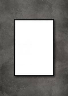 Black picture frame hanging on a dark concrete wall. blank mockup template