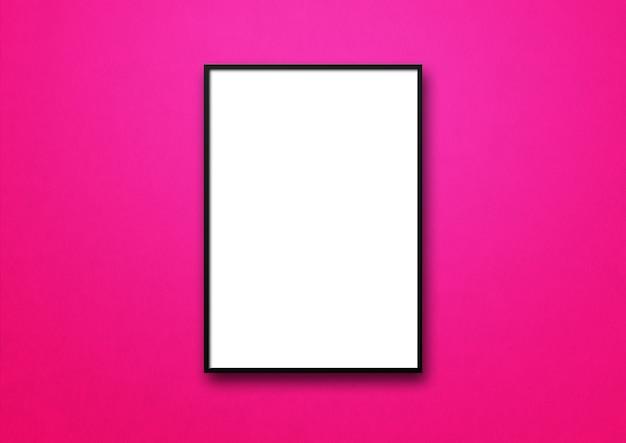 Черная фоторамка висит на розовой стене.