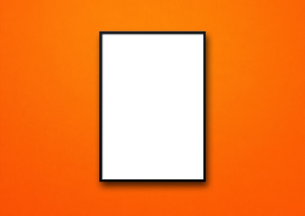 Black picture frame hanging on an orange wall.