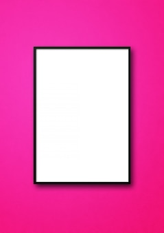 Black picture frame hanging on a pink wall. blank template