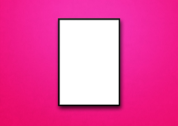 Black picture frame hanging on a pink wall.