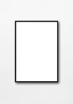 Black picture frame hanging on a white wall.
