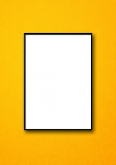Black picture frame hanging on a yellow wall. blank mockup template
