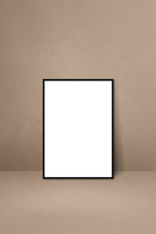 Black picture frame leaning on a beige wall. blank mockup template