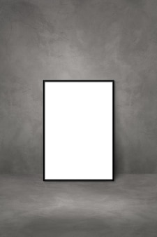 Black picture frame leaning on a dark concrete wall. blank mockup template