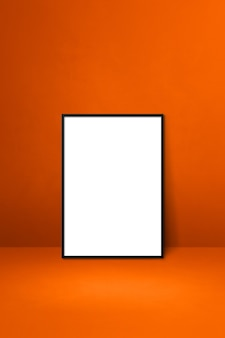 Black picture frame leaning on an orange wall. blank mockup template