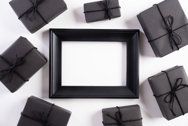 Black picture frame with gift box on white background. black friday