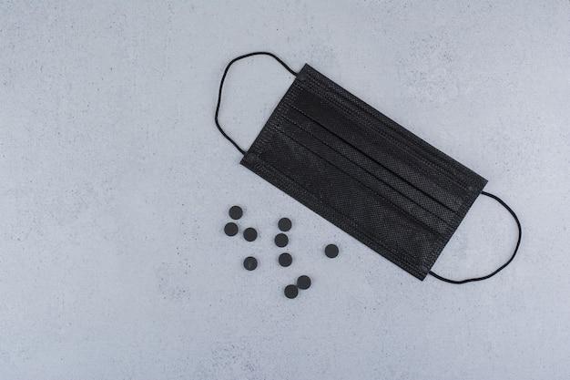 Pillola nera e mascherina medica sulla superficie di marmo.