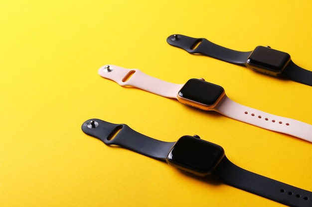 Black and pink smart watches on yellow background.