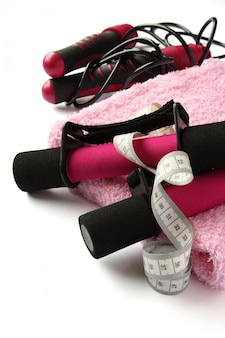 Black-pink soft dumbbell with handle strap, measuring tape, towel and skipping rope over white