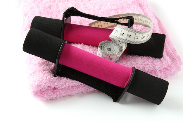 Black-pink soft dumbbell with handle strap and measuring tape on towel over white