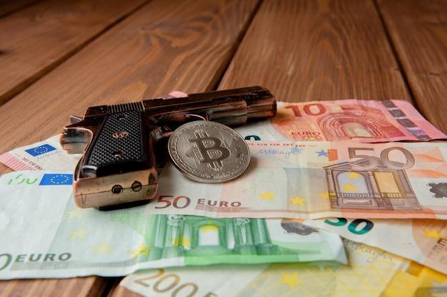 검은 권총, 유로 및 동전 형태의 비트 코인