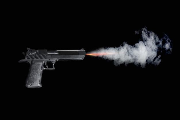 暗い背景に火と煙で射撃する黒いピストル。