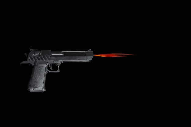 暗い背景に火を使って射撃する黒いピストル。