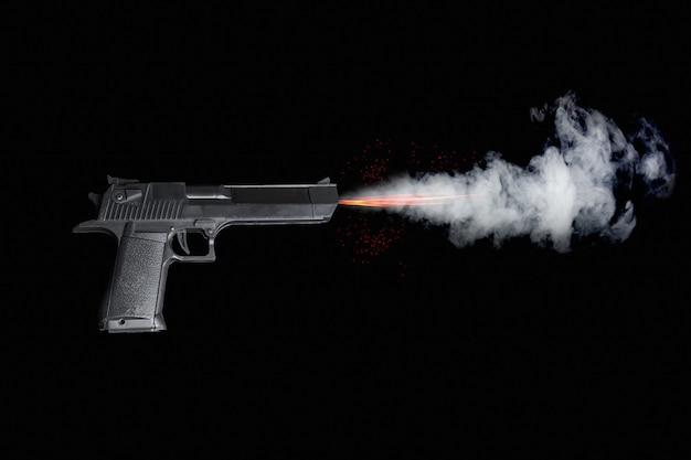 暗い背景に火、火花、煙で射撃する黒いピストル。