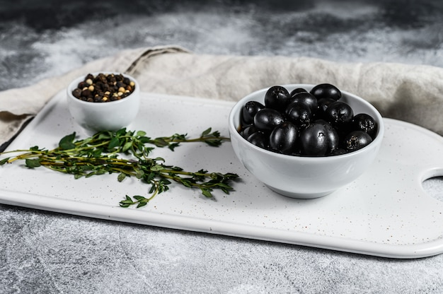 Black pitted olives on a white chopping board. gray background. top view