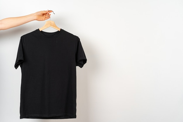 Black plain t-shirt hanging on a hanger, copy space