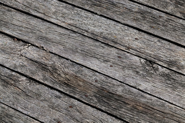 Black planks made of just a pier by the river in the countryside, a closeup of old wood for construction