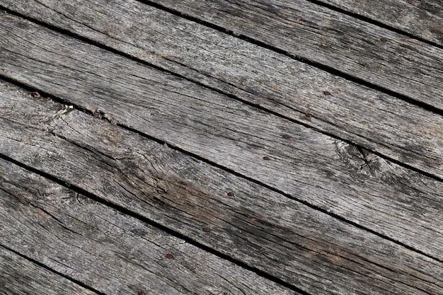 田舎の川沿いの桟橋だけで作られた黒い板、建設用の古い木のクローズアップ