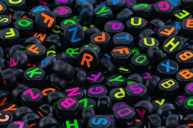色付きの文字がランダムに配置された黒いプラスチックビーズ。