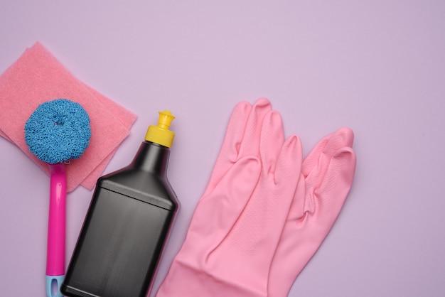 Черная пластиковая бутылка и розовые резиновые перчатки для чистки, кисти на фиолетовой поверхности, плоская планировка, набор для чистки