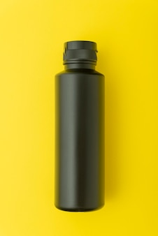 黄色の背景に黒いプラスチックボトルバイアル。モックアップ。