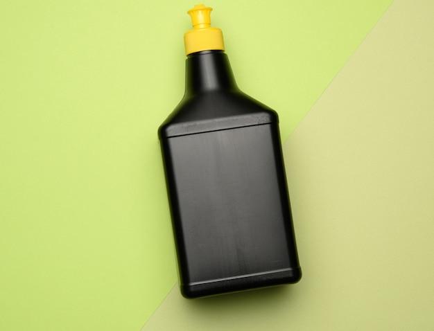 Черная пластиковая бутылка с моющим средством для мытья посуды и вещей в домашних условиях, предмет на зеленой поверхности