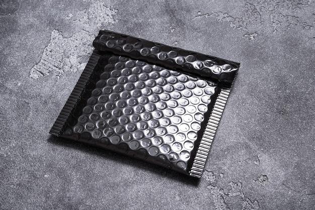灰色の背景に黒いプラスチックのバブル封筒