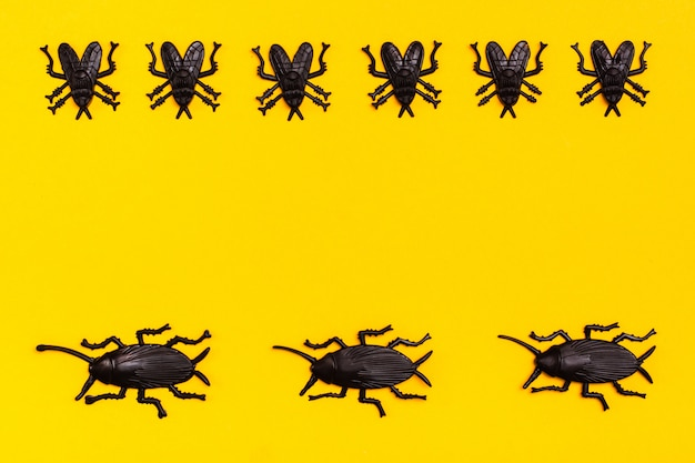 Black plastic cockroaches and black plastic flies on a yellow cardboard background. ready halloween illustration. copy space