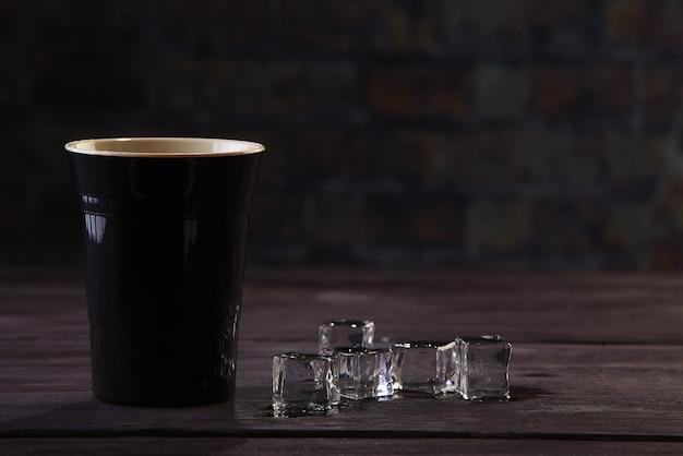 暗い木製の背景に黒いプラスチックカップと角氷