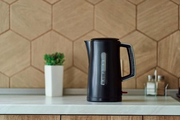 白いカウンタートップに黒いプラスチック製の電気ケトル。ホットドリンクを作るための家庭用キッチン家電