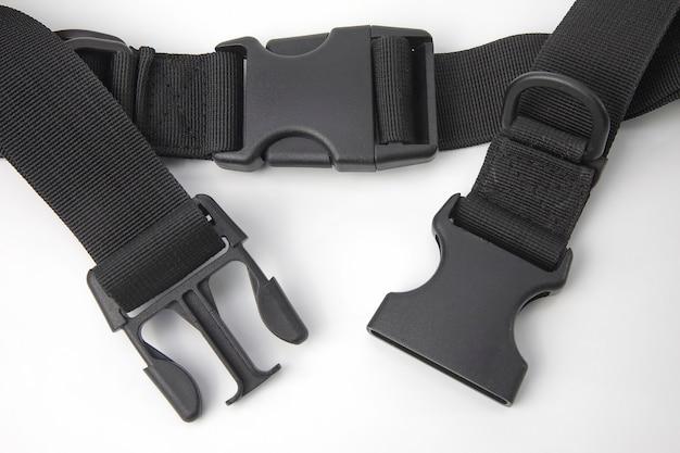 흰색 표면에 배낭 용 검은 색 플라스틱 fastex 클립. 의류 및 장비 품목