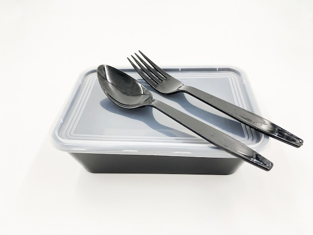 Black plastic food container with spoon and fork on white