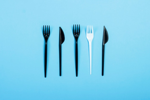 Black plastic forks and knives and one white plastic fork on a blue background. concept plastic, harmful, environmental pollution, stop plastic. flat lay, top view.
