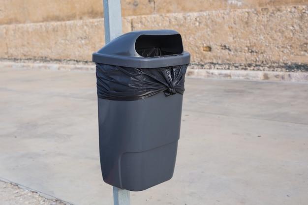 Черный пластиковый мусорный бак на улице.