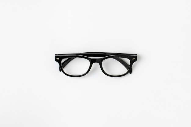 Black plastic glasses and a shadow on white background