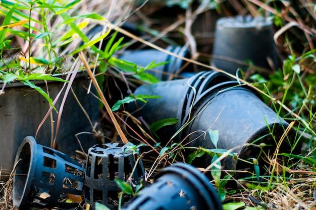 Черные пластиковые горшки для растений разбросаны по земле.