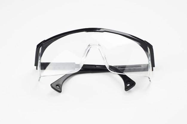 Черные пластиковые защитные очки на белом. концепция защиты спецодежды