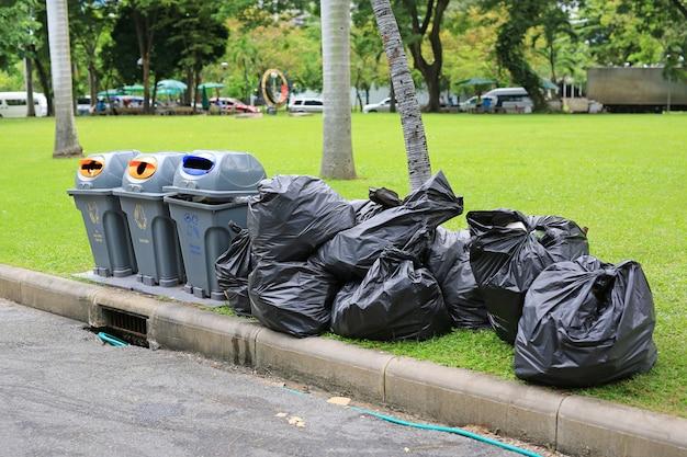 Black plastic trash bags on green grass garden near street.