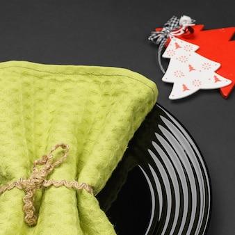 Черная тарелка и новогоднее украшение для праздничного меню