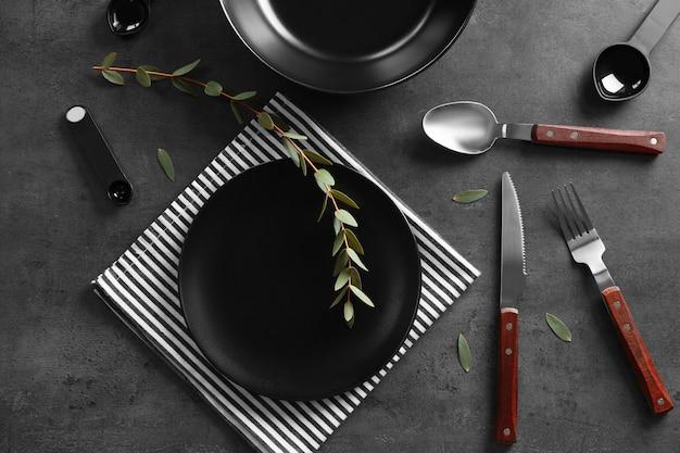 Черная тарелка и столовые приборы на сером столе, вид сверху